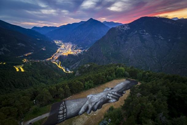 Primer pla de l'obra amb el fons de la ciutat d'Andorra la Vella.