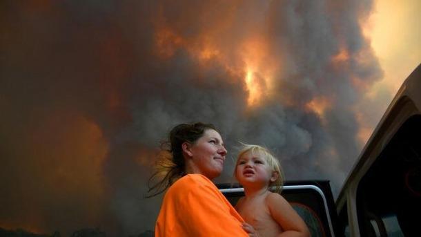 Una dona amb un infant sota el fum dels incendis a Austràlia.