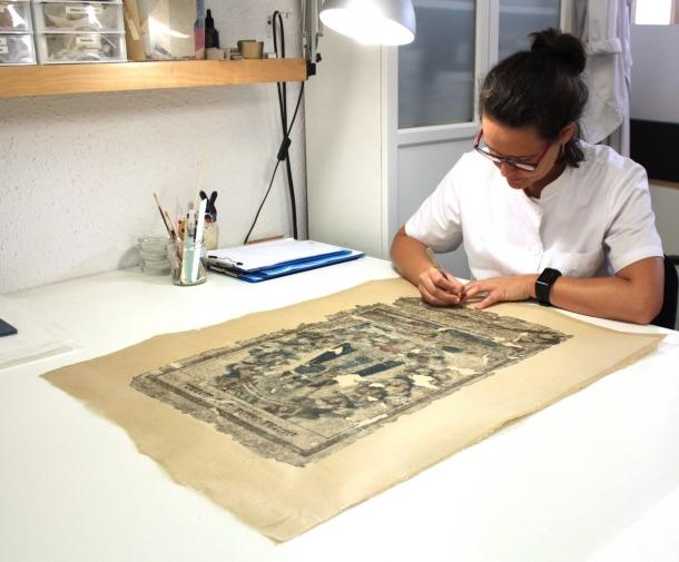 La restauradora Berta Blasi, al taller de Tiana, treballant en l'estampa.