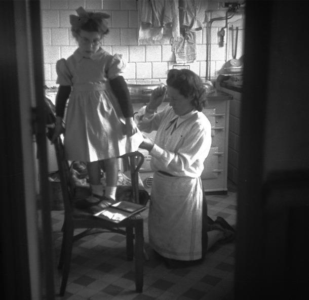 Anys 50: l'esposa de Josep Alsina cus la bata d'una veïneta enfilada a la cuina de la casa del fotògraf, a l'avinguda Carlemany d'Escaldes.