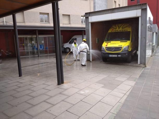 Dos funcionaris desinfectant l'exterior de l'hospital de la Seu.