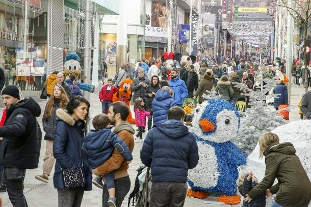 Els turistes omplen l'eix comercial i aprofiten per fer-se fotos amb la decoració nadalenca de fons.