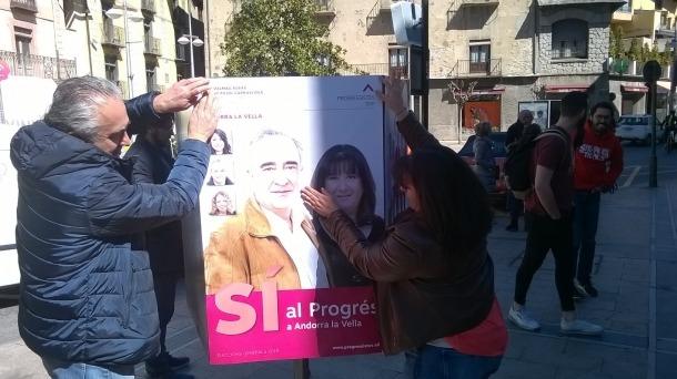 Àngel Dalmau i Meritxell Pujol enganxant el cartell de la territorial de Progressistes-SDP a la capital.