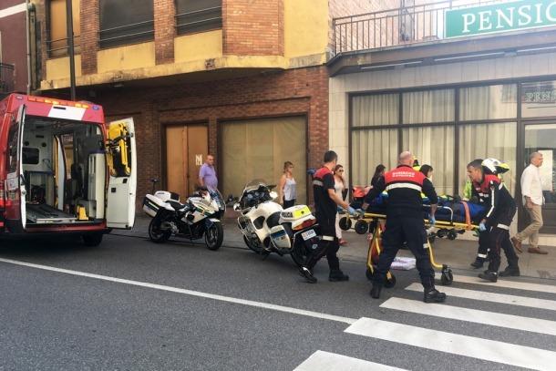 Els bombers traslladen un ferit a l'ambulància.