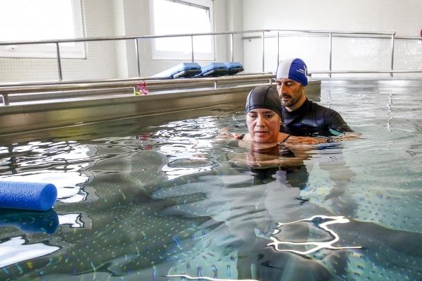Un pacient amb una malaltia neurològica fa hidroteràpia amb un fisioterapeuta a la nova piscina de l'hospital.