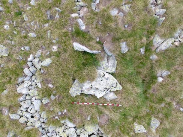 Perspectiva zenital del dolmen d'Encenrera, amb les lloses de la cambra i el cercle del cromlec clarament marcat: el pal fa dos metres.