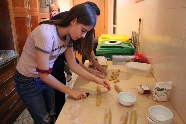 Joves i padrins fan panellets en un taller intergeneracional