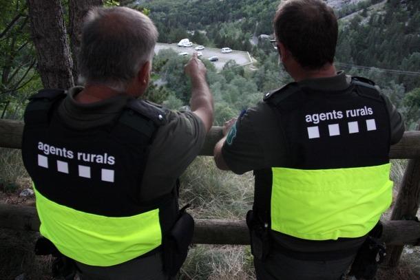 Dos agents rurals observant un dels aparcaments del Parc Nacional d'Aigüestortes.