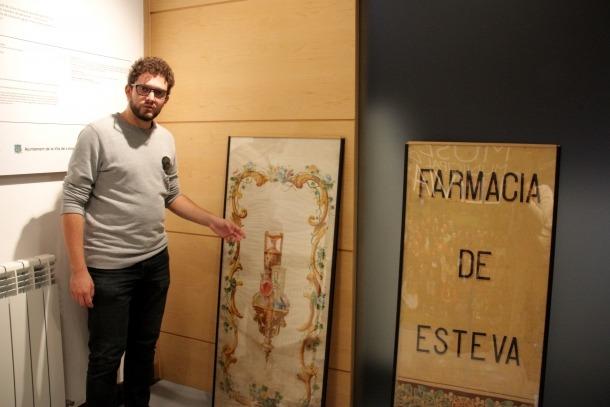 El director del Museu de Llívia, Gerard Cunill, mostrant les teles de l'antiga Farmàcia Esteva.