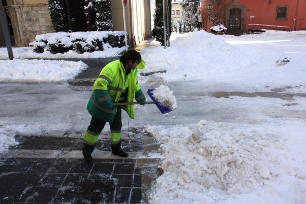 Un operari netejant la neu a la zona de la plaça dels Oms de la Seu.
