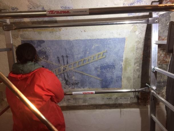 La restauradora Mireia Vidal neteja l'escala que els soldats van fer servir per despenjar Crist de la Creu.