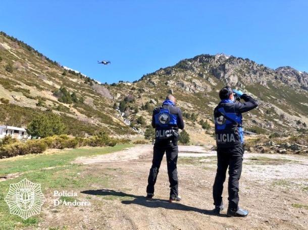 Dos agents de la policia fent vigilància amb l'ajuda d'un dron.