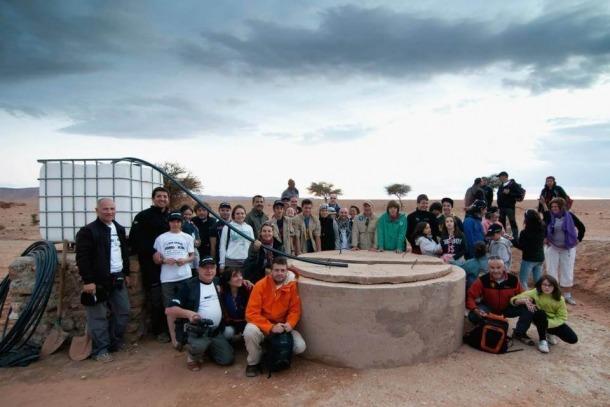 Participants del Raid Solidari i veïns d'Ouzina amb el pou d'aigua.