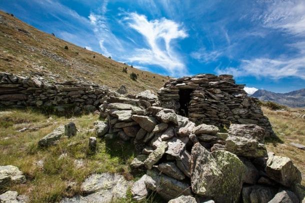 Cabana de l'orri de Rusca, a Canillo, adaptada al terreny i adossada a una roca.