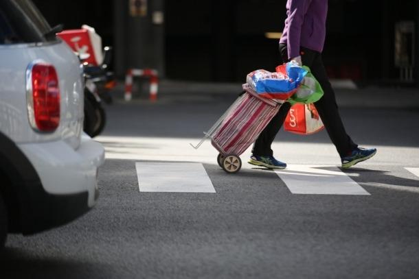 Una persona carregada amb la compra.