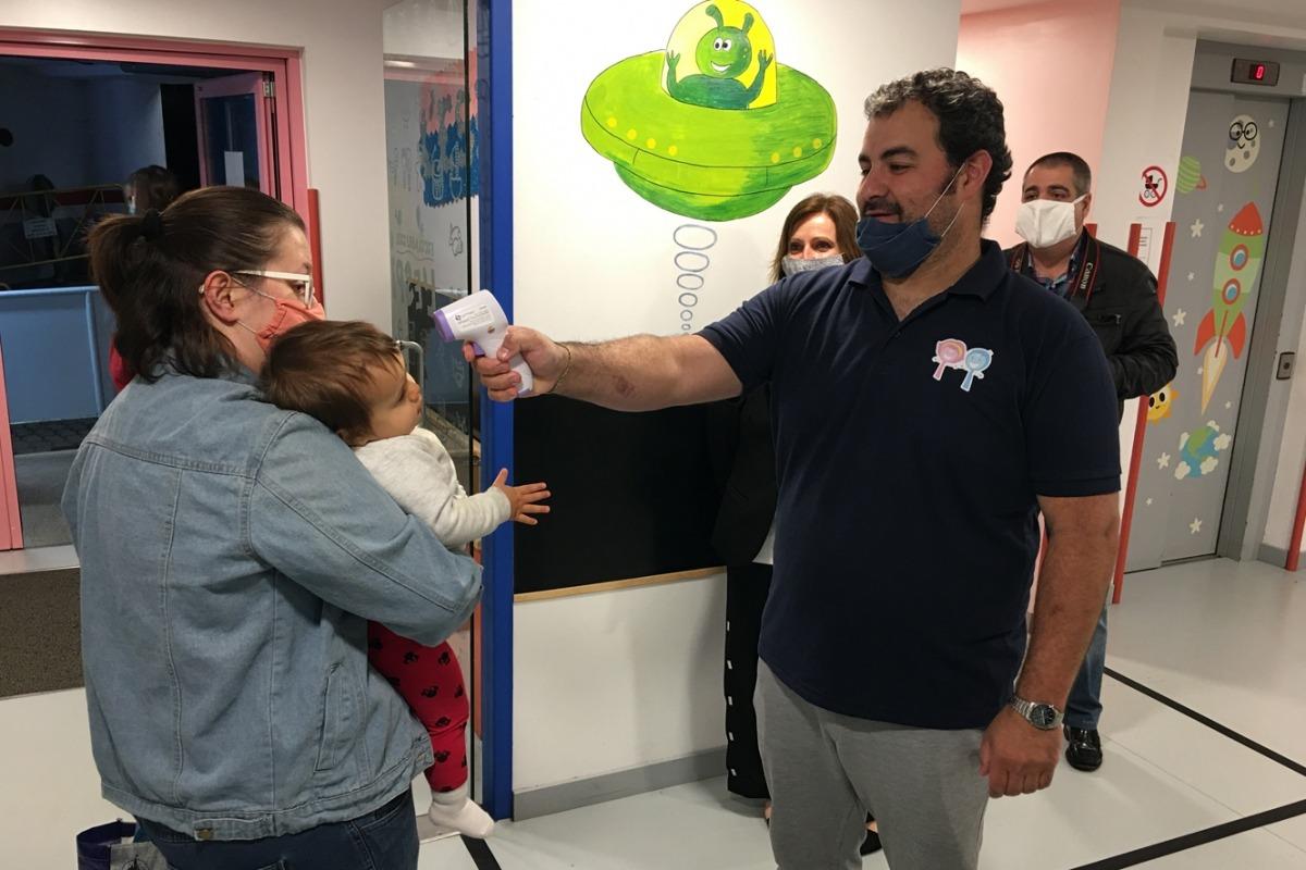 El director de l'escola bressol pren la temperatura a un infant.