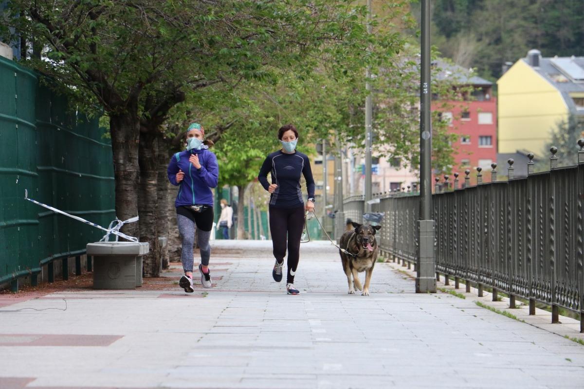 Dues persones corren amb el seu gos al costat del riu, al Parc Central de la capital.