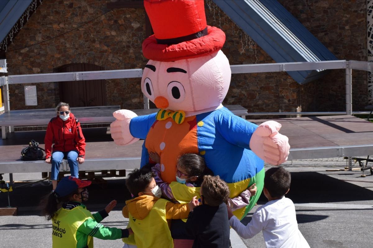 Infants abracen un dels personatges que ha participat en la desfilada.