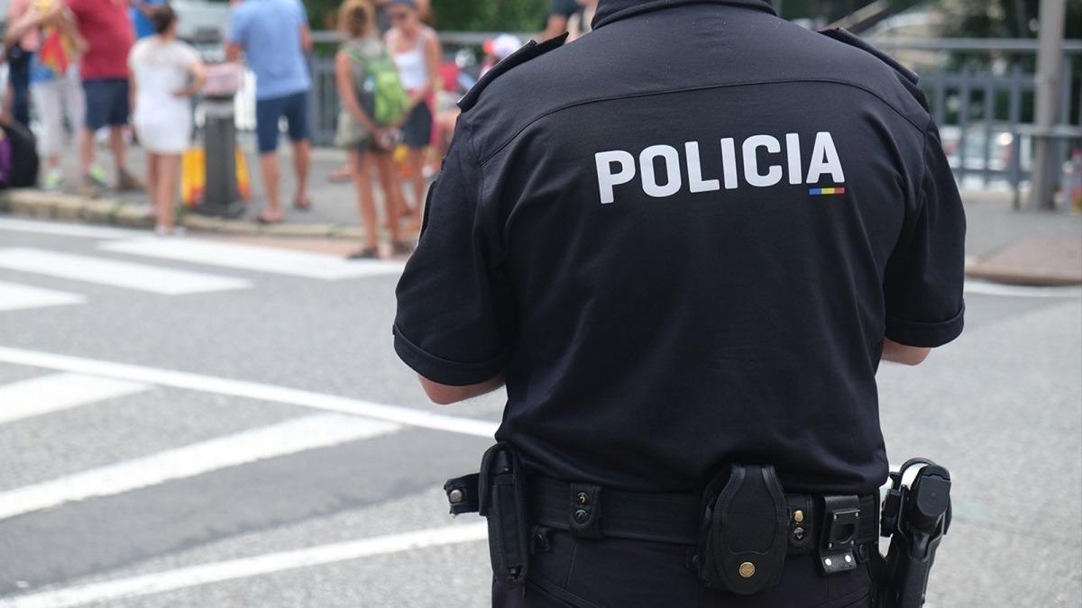 Un agent del cos de Policia d'esquenes.
