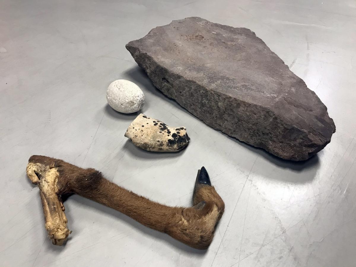 Pota de cabra, percussor de pedra, nucli de sílex i mola de gres.