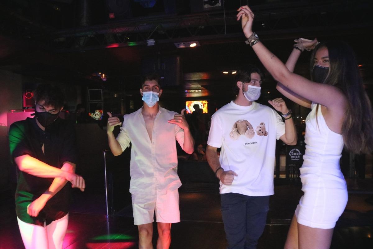Un grup de joves balla, amb mascareta, en una discoteca.