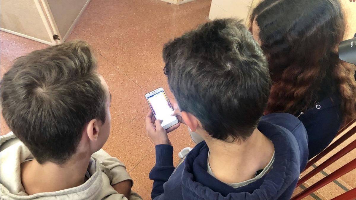 Alumnes d'una escola utilitzant el telèfon mòbil