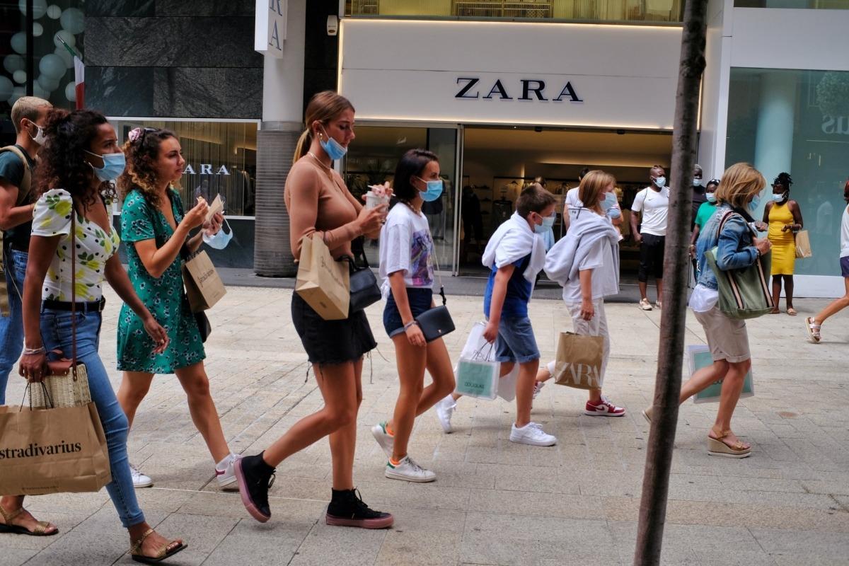 Joves caminen per l'eix comercial sense mascareta o amb aquesta sota la barbeta mentre mengen i beuen.