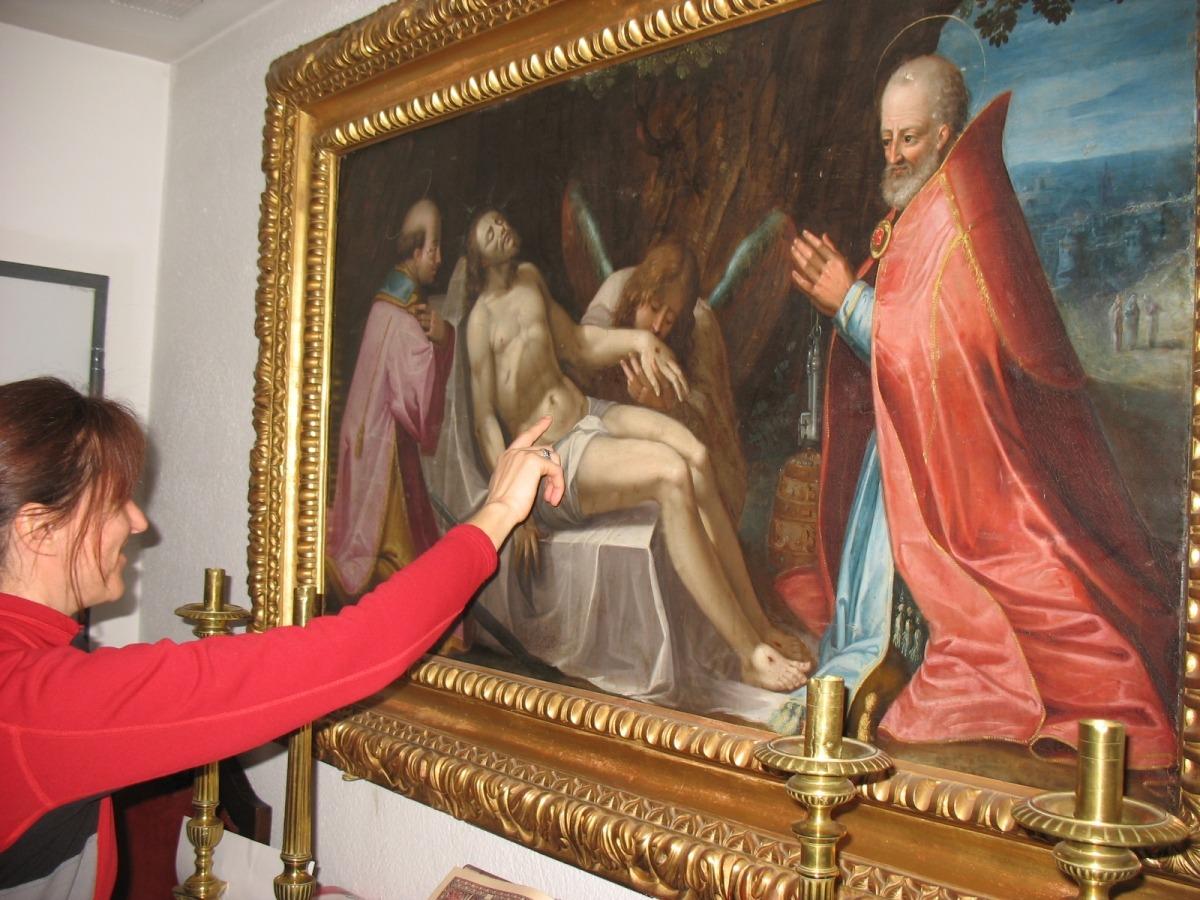 La restauradora Mireia Tarrés observa l''Enterrament', oli barroc que es conserva a la sagristia de Sant Esteve.