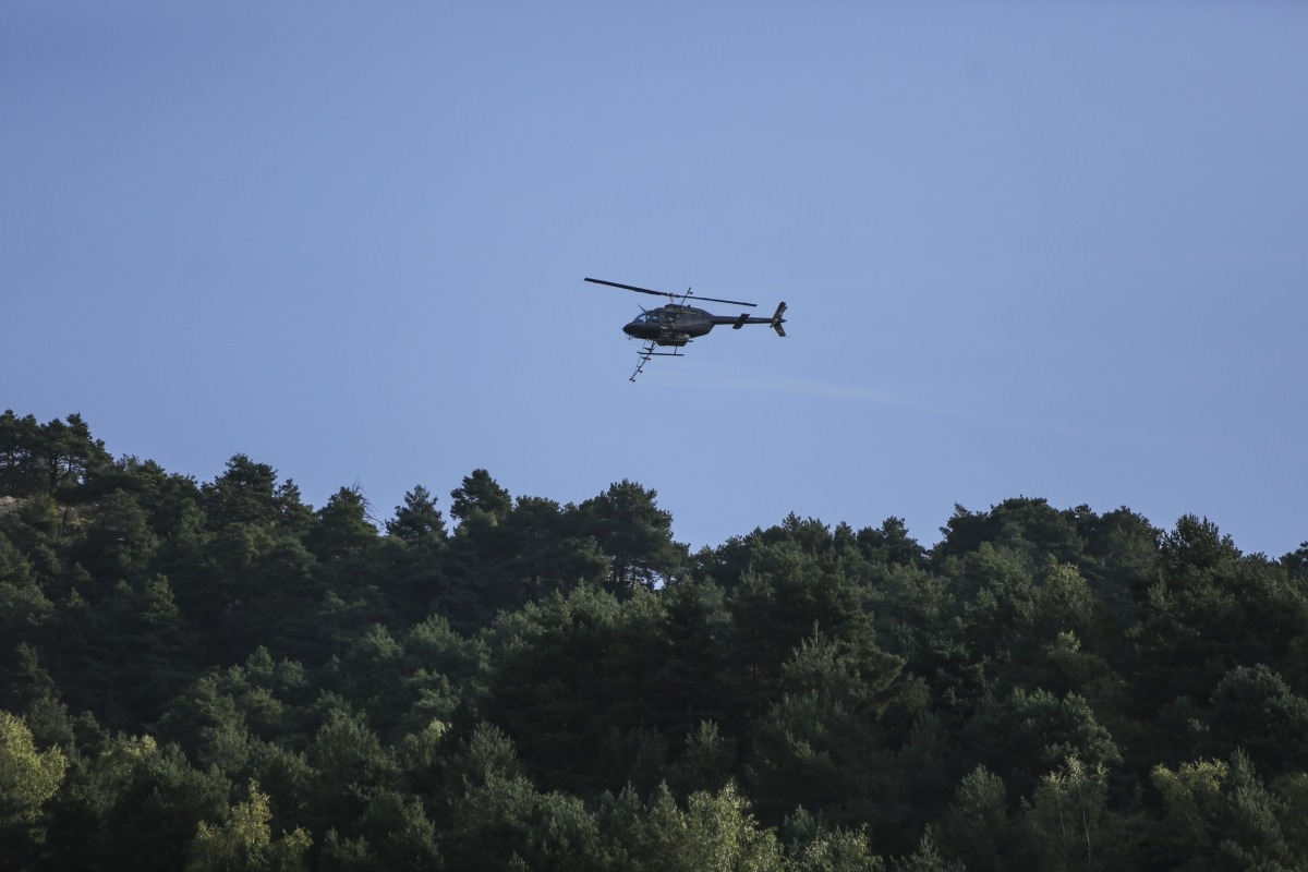 L'helicòpter encarregat de la fumigació sobrevolant boscos de la Massana, ahir.