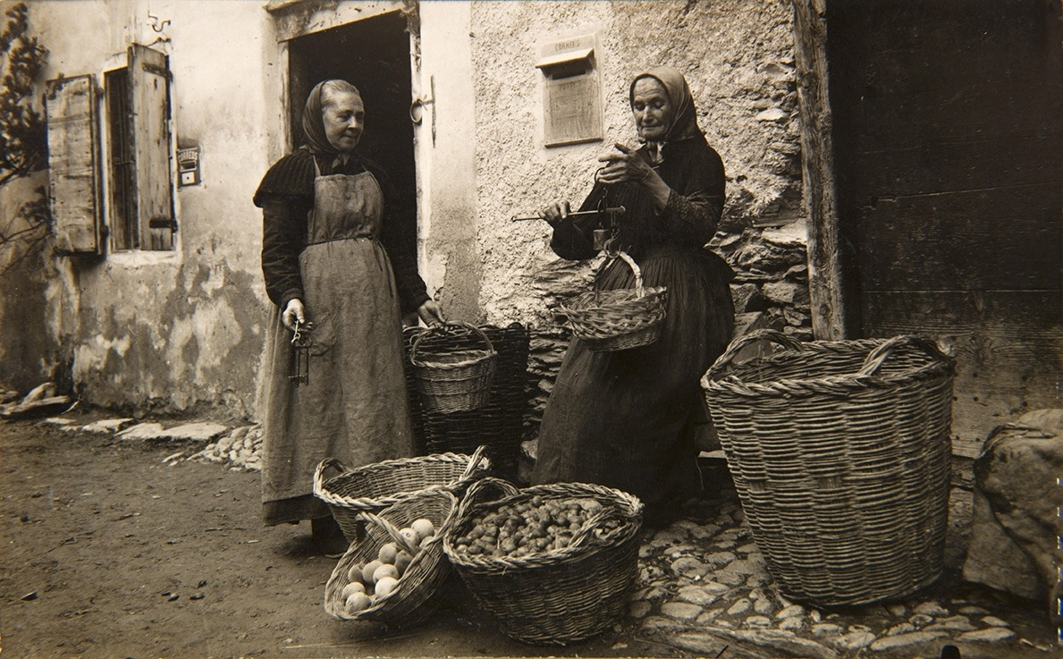 Venedora de verdura a la plaça d'Ordino, cap als anys 10 del segle XX: atenció a la romana.