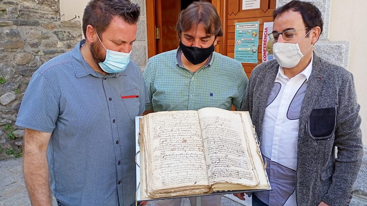 Lizarte, Valera i mossèn Pepe Chisvert observen el llibre d'òbits de Sant Julià, on consta la defunció de Simeó, el 27 d'agost del 1737.