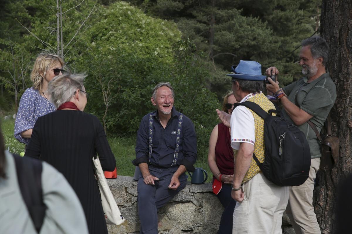 El britànic Bob Budd conversa (assegut) amb altres participants en la inauguració, artistes i convidats.