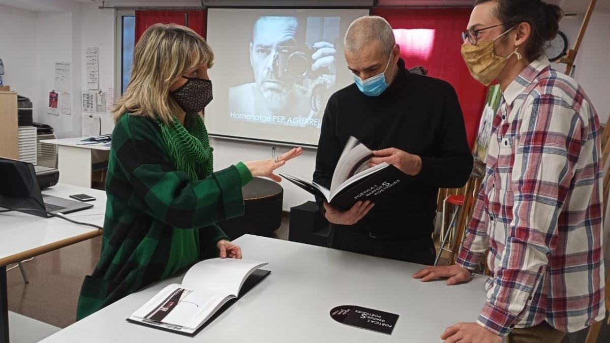 Mola, Tena i Casahuga observen uns exemplars de 'Poètica del paisatge' sota la mirada de Pep Aguareles.