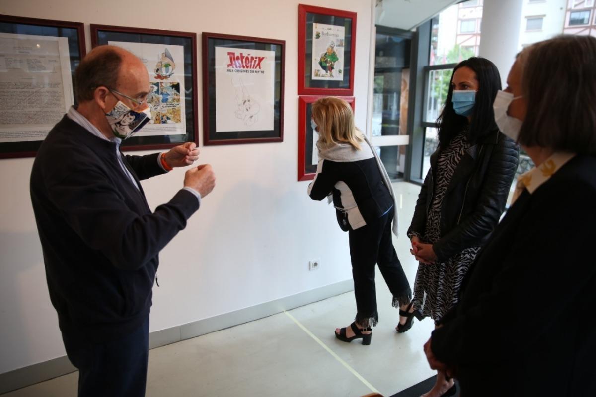 Pieras explica detalls de l'exposició a la cònsol Olga Molné i l'ambaixadora Jocelyne Caballero; la directora de Promoció Cultura, Montse Planelles, es mira les planxes.