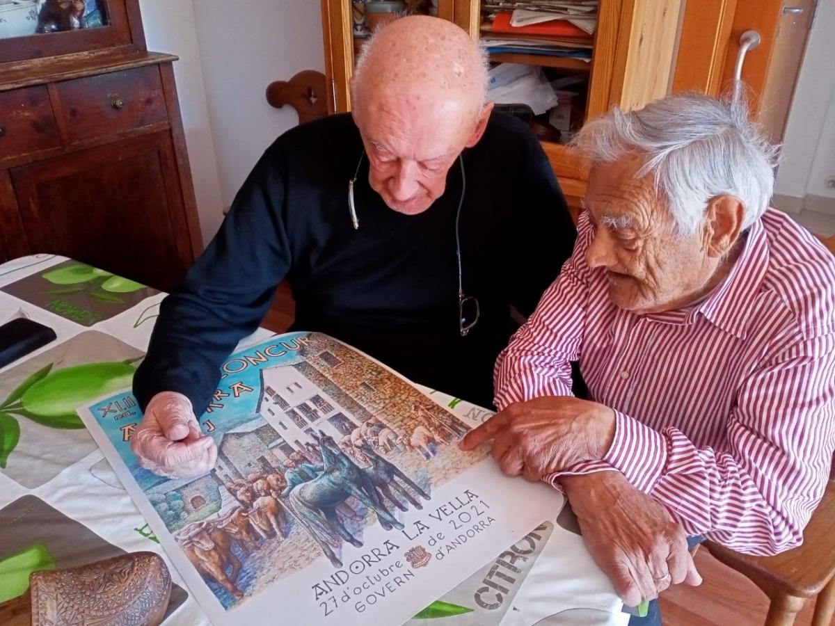 Casimir Arajol i Sergi Mas comenten el cartell d'aquest any, acabat de sortir de la impremta. L'original és a tinta xinesa i aquarel·la.