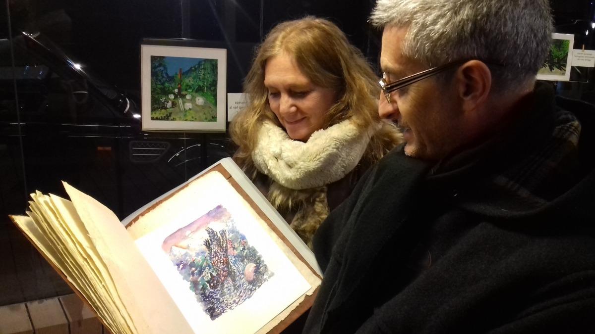 Loli Rodríguez i Manel Gibert contemplen els originals de Sergi mas per a 'Al sol que bat la penya'. Al fons, aquarel·la de Rodríguez.