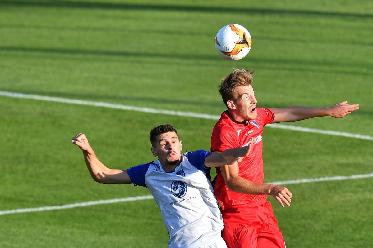 El defensa central de l'Inter Club Escaldes, Raul Feher, lluitant per una pilota àeria amb un jugador del Drita