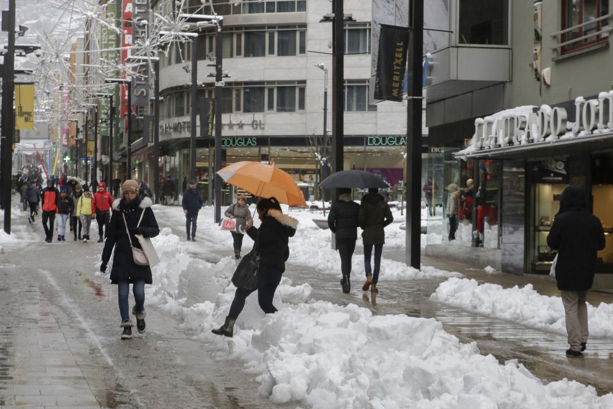 Vianants a l'avinguda Meritxell superant la neu acumulada al carrer.