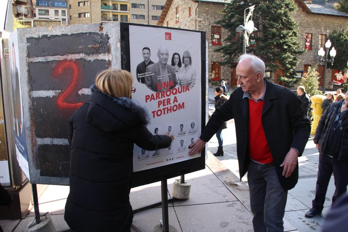 Maria Carme Sánchez Balletbó i Joan Travesset (Units pel Canvi) van enganxar els cartells a la plaça de la Germandat.