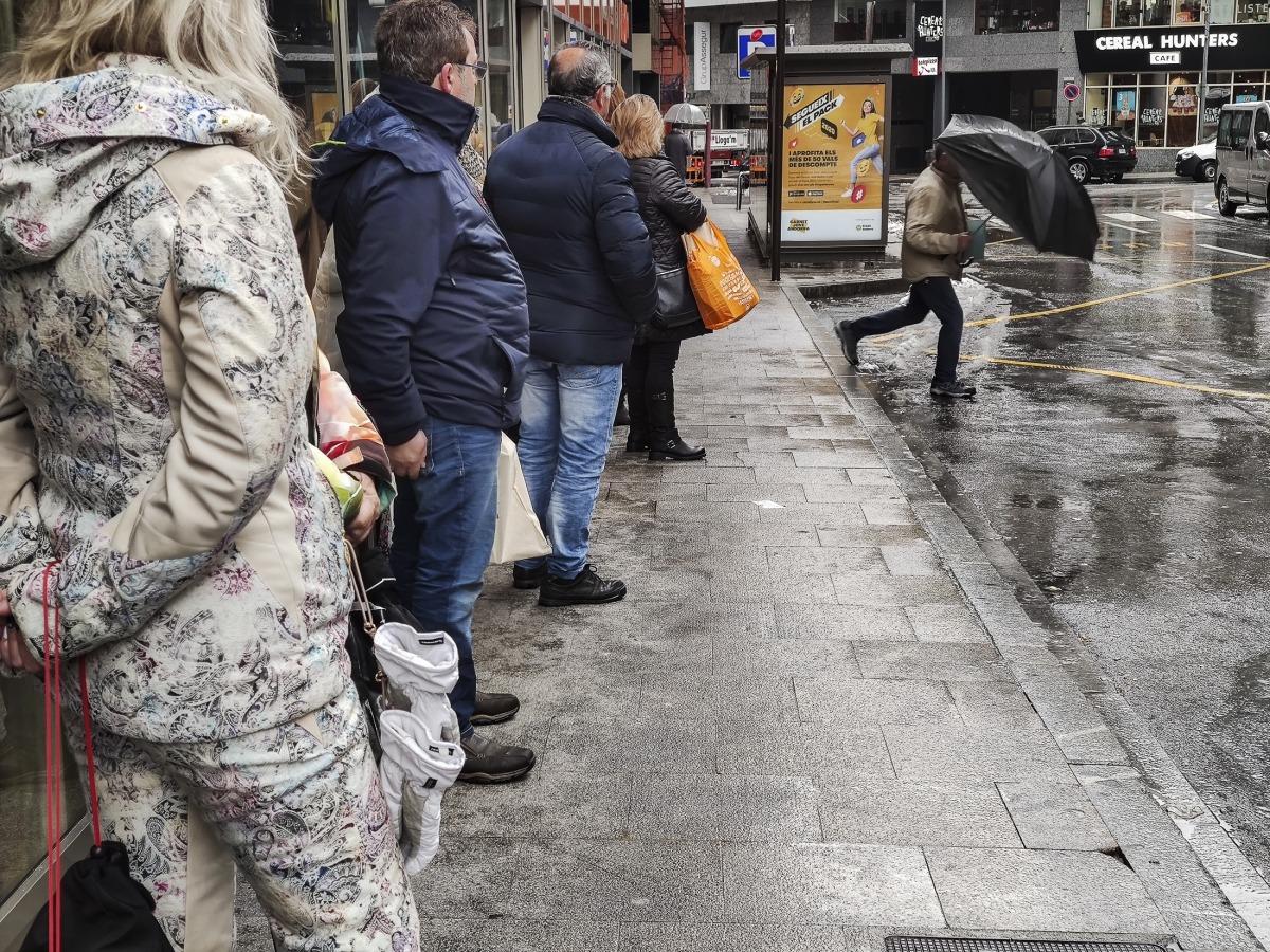 Un grup de persones esperen l'autobús en una parada d'Andorra la Vella.