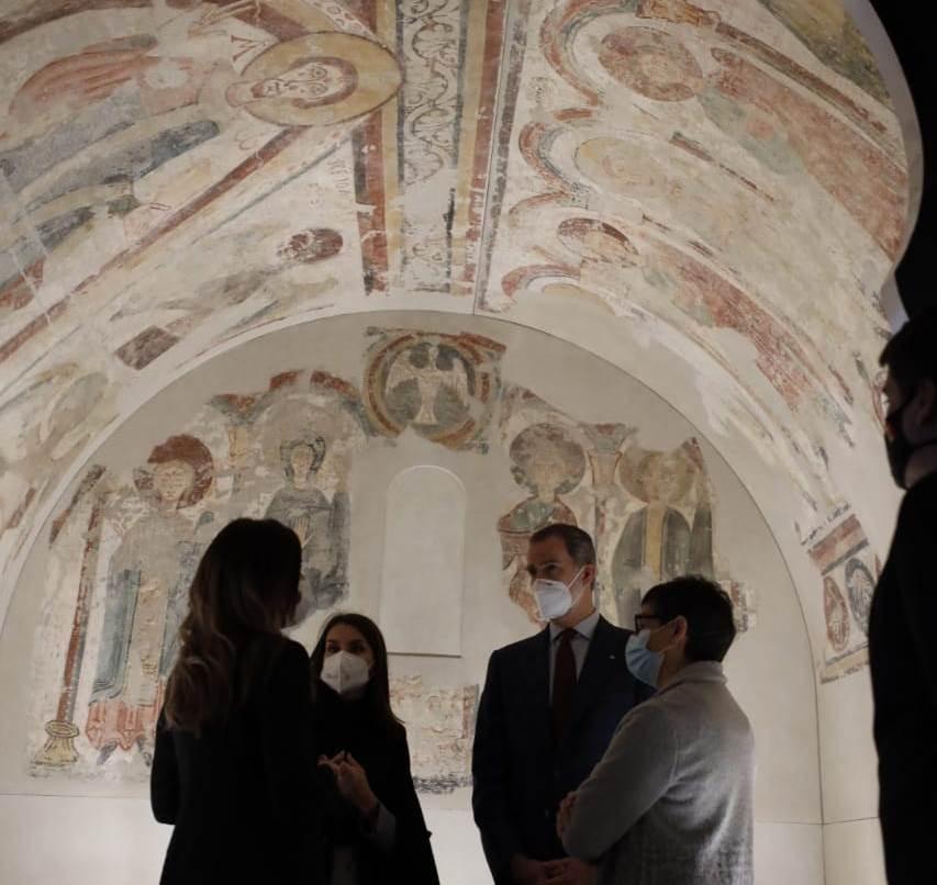 Els reis, amb la ministra d'Exteriors espanyola, atenen les explicacions de la ministra de Cultura, Sílvia Riva, davant dels frescos de l'absis de Santa Coloma.