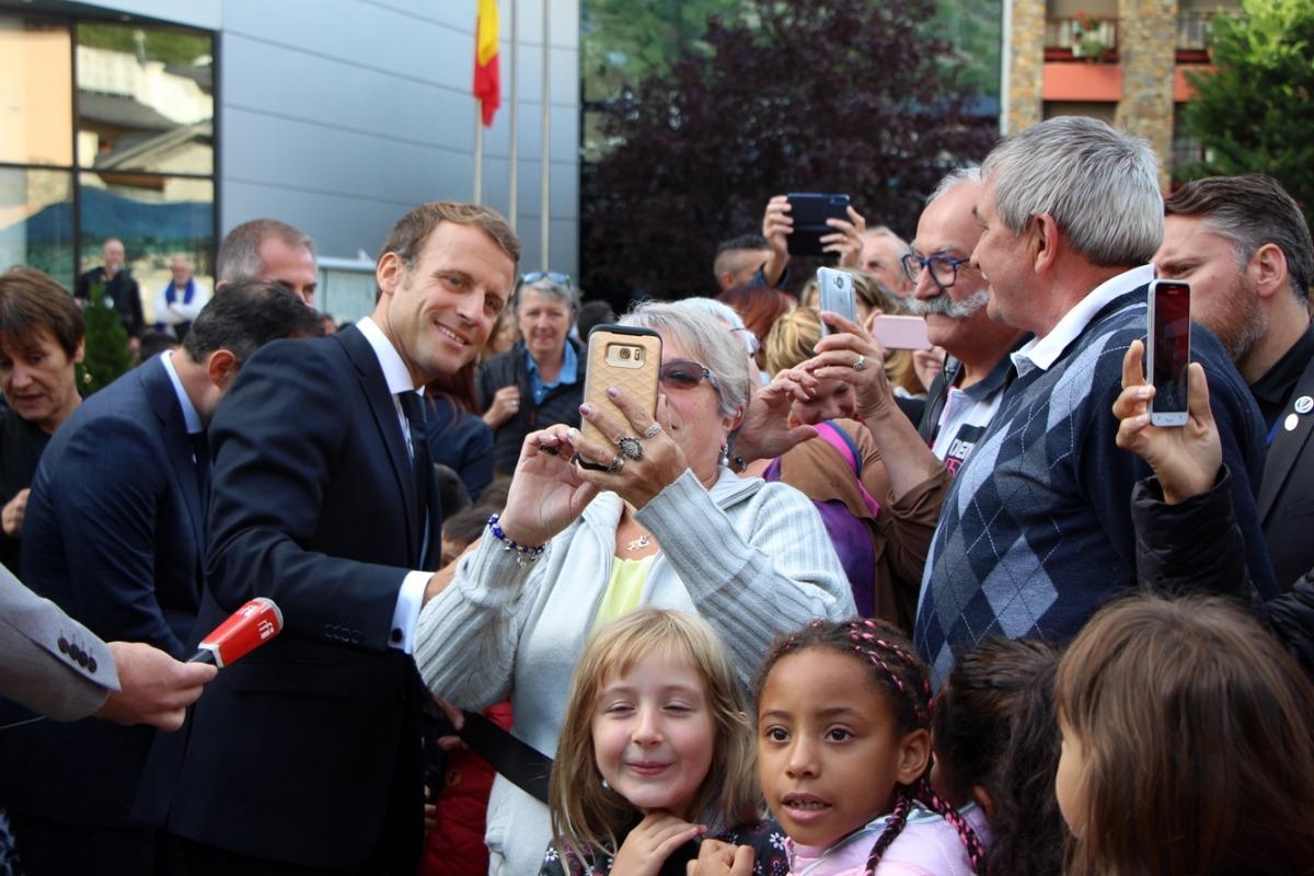 El copríncep francès va accedir a fer-se una selfie amb una encampadana, en la visita de divendres a la parròquia.
