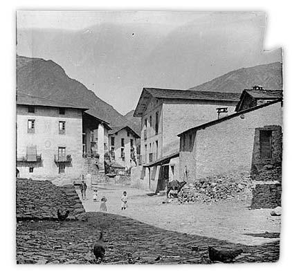 La plaça Benlloch cap al 1900, quan de fet encara no es deia així. La rectoria, la carnisseria i la presó, amb porta i dues finestretes: el calabós es va excavar a la penya que hi ha a sota.