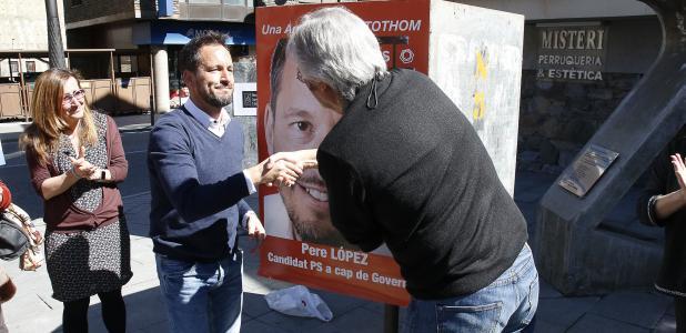 Pere López i Vicenç Alay penjant el cartell del PS a la Massana.
