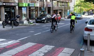 Uns ciclistes circulant pel carrer Prat de la Creu.