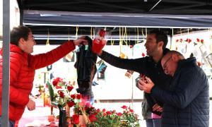 Un home adquirint una rosa a la fira d'Escaldes-Engordany.
