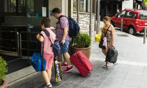 Turistes al davant d'un hotel.