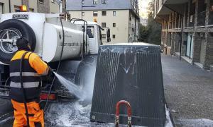 Un operari utilitzant aigua amb alta pressió per a la neteja dels carrers.