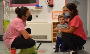 Una mare recull el seu fill a l'escola bressol.