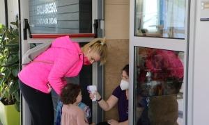 Una treballadora de l'escola bressol pren la temperatura a una nena abans d'entrar al recinte.
